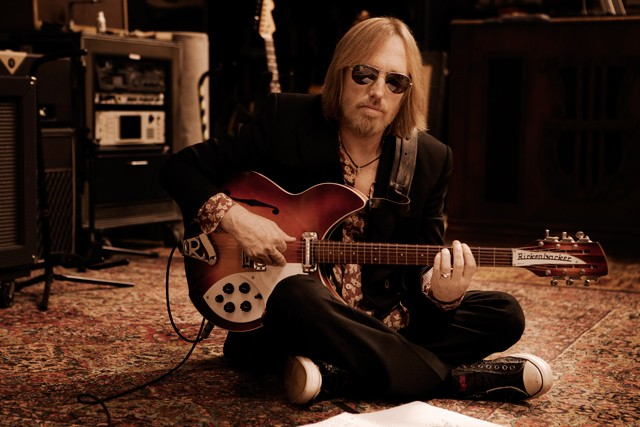 Tom Petty Sitting on the Floor with His Guitar